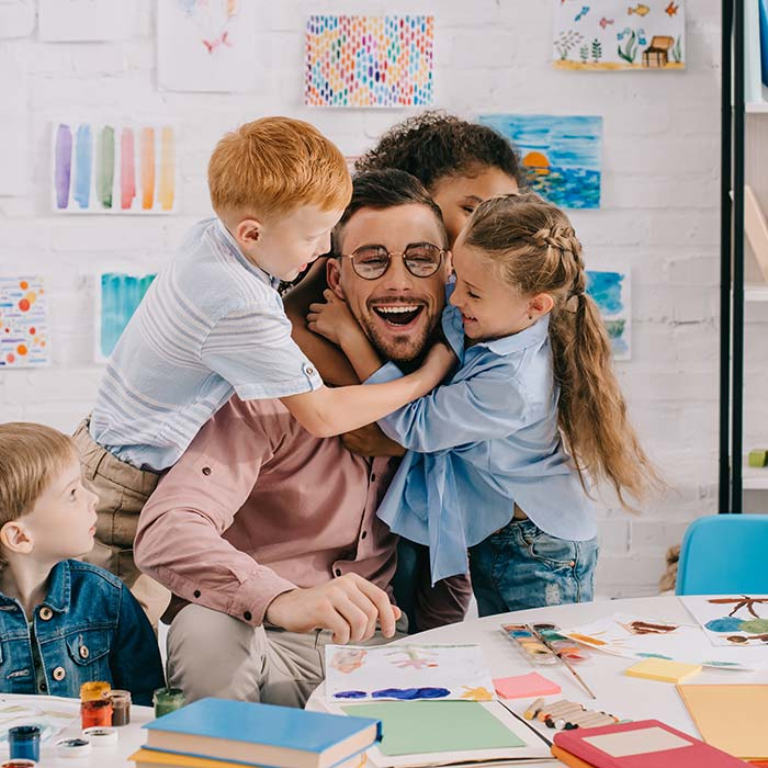 Male teacher in a classroom with kids hugging him